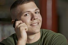 Hombre joven que habla en smartphone Fotografía de archivo
