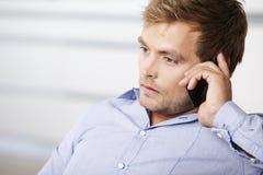 Hombre joven que habla en su teléfono móvil Foto de archivo libre de regalías