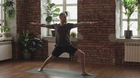 Hombre joven que hace actitud de la yoga del guerrero en estudio con el piso de madera y las ventanas grandes almacen de video