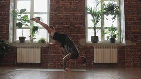 Hombre joven que hace asana Actitud de la situaci?n de la mano Entrenamiento del amo de la yogui en estudio urbano almacen de metraje de vídeo