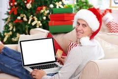 Hombre joven que hace compras en línea con la tarjeta de crédito en casa para la Navidad Fotos de archivo libres de regalías