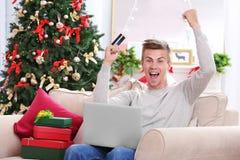 Hombre joven que hace compras en línea con la tarjeta de crédito en casa para la Navidad Fotografía de archivo