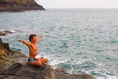 Hombre joven que hace ejercicio de la yoga en la playa del mar Imagenes de archivo