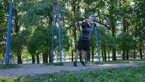 Hombre joven que hace ejercicios del pectoral en lazos de la aptitud en un parque del verano cantidad de la vista delantera de la metrajes