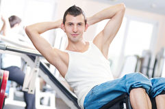 Hombre joven que hace ejercicios en la gimnasia Fotografía de archivo