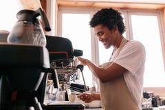 Hombre joven que hace el café con una máquina del café del café express en el café Foto de archivo libre de regalías