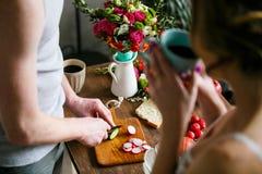 Hombre joven que hace el desayuno así como su novia imagenes de archivo