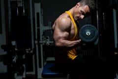 Hombre joven que hace el ejercicio pesado para el bíceps Imágenes de archivo libres de regalías
