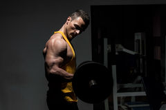 Hombre joven que hace el ejercicio pesado para el bíceps Imagen de archivo