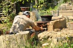 Hombre joven que hace el fuego para cocinar afuera Imágenes de archivo libres de regalías