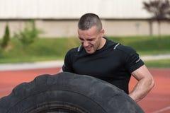 Hombre joven que hace el neumático Flip Workout Outdoor Imágenes de archivo libres de regalías