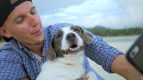 Hombre joven que hace el retrato de Selfie con su perro en la playa tailandia HD a cámara lenta almacen de video