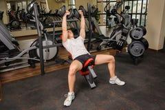 Hombre joven que hace entrenamiento de la prensa de banco de pendiente de la pesa de gimnasia en gimnasio Fotografía de archivo libre de regalías