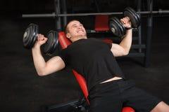 Hombre joven que hace entrenamiento de la prensa de banco de pendiente de la pesa de gimnasia en gimnasio Imágenes de archivo libres de regalías