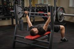 Hombre joven que hace entrenamiento de la prensa de banco en gimnasio Foto de archivo