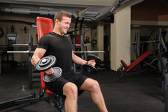 Hombre joven que hace entrenamiento del bíceps de la pesa de gimnasia en gimnasio Foto de archivo