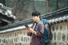 Hombre joven que hace excursionismo en Corea Usando una tableta que se inclina contra una pared Foto de archivo libre de regalías