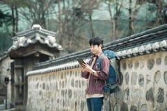 Hombre joven que hace excursionismo en Corea Usando una tableta que se inclina contra una pared Fotografía de archivo libre de regalías