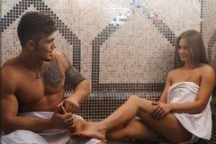 Hombre joven que hace masaje atractivo del pie de la muchacha en sauna Fotos de archivo