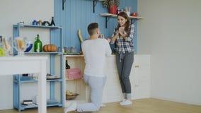 Hombre joven que hace oferta a su novia en la cocina en casa fotografía de archivo