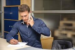 Hombre joven que hace papeleo en el escritorio de oficina, escribiendo Imágenes de archivo libres de regalías