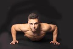 Hombre joven que hace pectorales Imagen de archivo libre de regalías