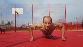 Hombre joven que hace pectorales afuera para el entrenamiento de Crossfit almacen de video