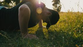 Hombre joven que hace pectorales en el césped en un parque público natural almacen de video