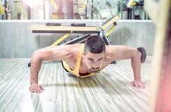 Hombre joven que hace pectorales en gimnasio Foto de archivo