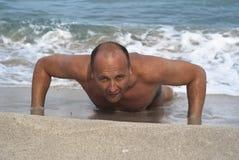 Hombre joven que hace pectorales en la playa Imagen de archivo libre de regalías