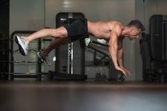Hombre joven que hace pectorales extremos en piso Fotografía de archivo