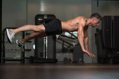 Hombre joven que hace pectorales extremos en piso Foto de archivo