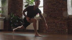 Hombre joven que hace un asana Hombre deportivo que hace yoga en estudio con el piso de madera almacen de metraje de vídeo