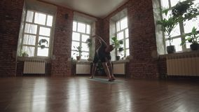 Hombre joven que hace un asana Entrenamiento del amo de la yogui en la estera negra en estudio urbano almacen de video