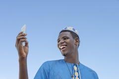 Hombre joven que hace un autorretrato con su teléfono móvil debajo de un cielo azul Fotos de archivo libres de regalías