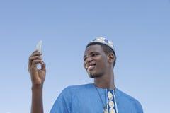Hombre joven que hace un autorretrato con su teléfono móvil debajo de un cielo azul Foto de archivo