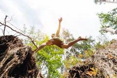 Hombre joven que hace un salto en el bosque fotografía de archivo libre de regalías