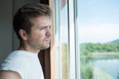 Hombre joven que hace una pausa la ventana por mañana Él se levanta temprano Imagen de archivo