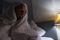 Hombre joven que hace una pausa la ventana por mañana Él se levanta temprano Imagen de archivo libre de regalías