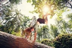 Hombre joven que hace una posición del pino en un tronco de árbol en el bosque imagenes de archivo