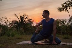 hombre joven que hace yoga cerca de la palmera en la puesta del sol fotos de archivo