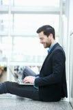 Hombre joven que hojea Internet en el ordenador portátil Imágenes de archivo libres de regalías