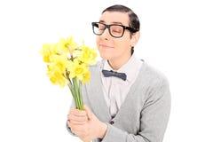 Hombre joven que huele un manojo de tulipanes amarillos Foto de archivo libre de regalías