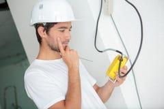 Hombre joven que instala el zócalo en la pared en casa fotos de archivo libres de regalías