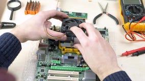 Hombre joven que instala una fan m?s fresca de la CPU en la placa madre almacen de video