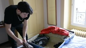 Hombre joven que intenta cerrar su maleta almacen de metraje de vídeo