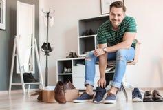 Hombre joven que intenta en los zapatos foto de archivo libre de regalías