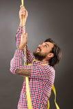 Hombre joven que intenta subir un concepto del cuerda-negocio Imagenes de archivo