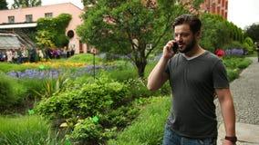 Hombre joven que invita al teléfono cerca de las flores en el jardín Plantas en el fondo metrajes