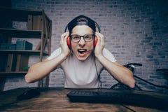 Hombre joven que juega al juego en casa y que fluye el playthrough o el paseo Foto de archivo